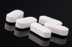 White pills on black Royalty Free Stock Images