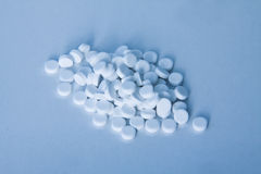 White pills on blue background Royalty Free Stock Photo