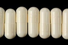 White Pills (Capsules) on Black Background Stock Photos