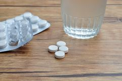 White pills displayed with a glass of water and two blister packs Stock Images