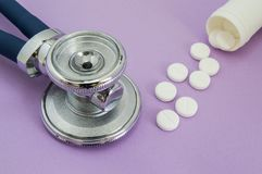 White pills falling out of a plastic tube or jar and the head of the stethoscope on a purple background. Frame or picture for to t. He internal medicine or Royalty Free Stock Photo