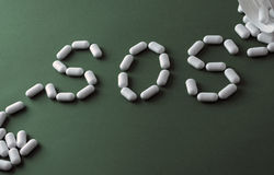 White pills on green background, which forming the word - SOS, with a blister of pills on background. Pharmaceutical or addiction narcotic or depressive or royalty free stock photo