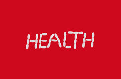 White pills health sign on red background Royalty Free Stock Photos