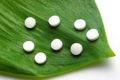 White pills on leaf stock photo