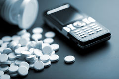 White pills and mobile phone. Calling for medical help: white pills and mobile phone Royalty Free Stock Photography