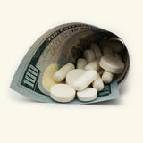 White pills with money. Health costs a lot Royalty Free Stock Images