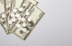 White pills and money, health expense concept,  care cost, Royalty Free Stock Photo