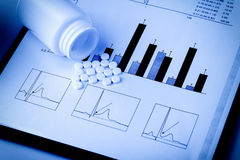 White pills and printed medical graphs Stock Images