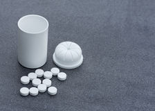White Pills scattered across a Gray Background and an Open Bottle. Top View Closeup. Stock Photo