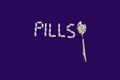 White pills sign with spoon  on violet background Stock Photo