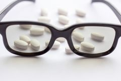 White pills and tablets with glasses on light background. Pharmacy and medicine for eyes concept stock images