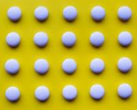 White pills on the yellow background. White round pills on a yellow background royalty free stock photo