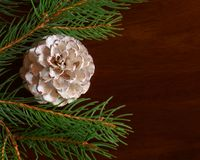 White pine cone among Christmas tree branches. On a wooden surface Stock Image