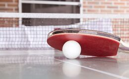 White Pingpong Ball Beneath Red Table Tennis Paddle Stock Images