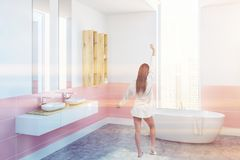 White and pink bathroom corner, white tub, girl. Woman in a modern bathroom corner with white and pink walls, a concrete floor, a white bathtub standing under royalty free stock photography