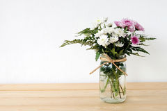 White and pink daisy bouquet in mason jar on table background Royalty Free Stock Photos