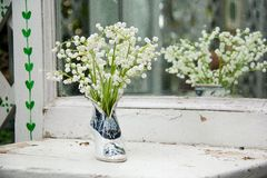 White and pink flowers on light vintage windowsill. Beautiful bouquet of bright wildflowers stock images
