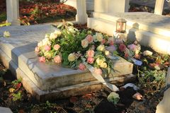 Funeral flowers on a tomb. White and pink funeral flowers on a marble tomb royalty free stock photos