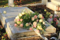 Funeral flowers on a tomb. White and pink funeral flowers on a marble tomb royalty free stock photo