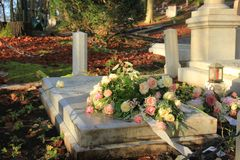 Funeral flowers on a tomb. White and pink funeral flowers on a marble tomb stock photos