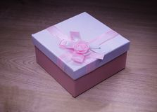 White - pink gift box on a wooden background Royalty Free Stock Photo