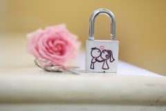 White and Pink lock of a newly-married couple with funny picture. White and Pink lock of a newly-married couple with kissing bride and groom stock photos