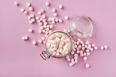 White and pink marshmallows in glass jar on pink background stock image