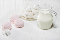 White and pink marshmallows and a jug of milk on a white wooden table. Food. White and pink marshmallows and a jug of milk on a white wooden table. Beautiful Stock Image