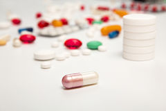 White pink medicine capsul on foreground. Heap of tablets backgr Royalty Free Stock Images