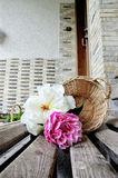 White and pink peonies, with basketat the entrance of a house Royalty Free Stock Photo