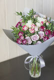 The bouquet of white and pink spray roses in gray floral paper Royalty Free Stock Image