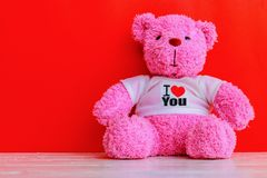 White and pink teddy bear. With red heart on red background. Valentine`s day concept royalty free stock image