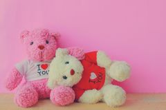 White and pink teddy bear. With red heart on red background. Valentine`s day concept stock photography