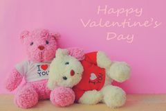 White and pink teddy bear. With red heart on red background. Valentine`s day concept stock photos