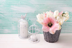 White and pink  tulips and narcissus in  grey bucket, candles in Stock Image