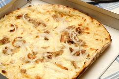 White pizpizza with tuna, onions and mozzarella. White pizza (no tomato) cooked and served in cardboard Royalty Free Stock Image