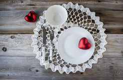White place setting with two red hearts sitting on white lace doily on wood background. Royalty Free Stock Photo