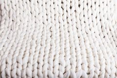 White plaid big knit. texture pigtail knitted blanket. The texture of fabric thick beige sweater close-up. Knitted texture background. white plaid big knit Royalty Free Stock Image