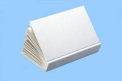 White plain book for design layout. Open white book isolated on blue background, slightly open, ideal for graphic design royalty free stock photography