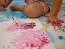 A white plain paper being painted by a little baby using a small brush. Selective focus of a white plain paper being painted by a little baby using a small brush royalty free stock image