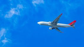White plane flying over a beautiful blue sky royalty free stock image