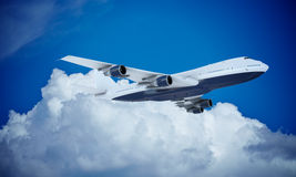 White plane flying in sky and clouds. Airplane boeing 747 Stock Photo