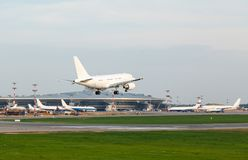White plane lands on the runway on the background of airport Stock Photography