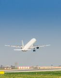 White plane takes off from air port. White plane takes off from an air port Royalty Free Stock Image