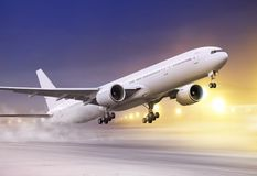 White plane in winter blizzard. Airport and white plane taking off at not flying weather, snowstorm Stock Image
