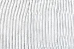 White plaster cement structure with relief curved strips. Background texture of vertical cement uneven wavy strips stock images