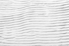 White plaster cement structure with relief curved strips. Background texture of horizontal cement uneven wavy strips stock photo