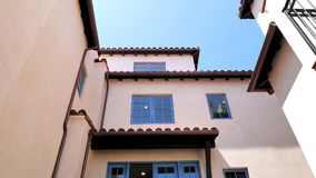 White Plaster Facade with Blue Windows and Spanish Tile Roof stock images
