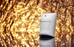 White plastic alarm motion sensor with fancy shiny gold background full of sparks out of focus. Stock Images