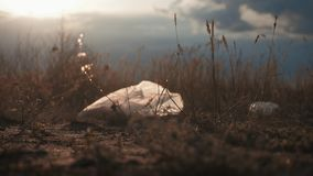 White plastic bag on the meadow in the sunset. Plastic pollution concept. Harm to the planet.
